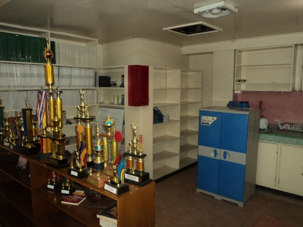 Storage area in the kitchen section. The present materials (trophies and yearbooks) will be removed.